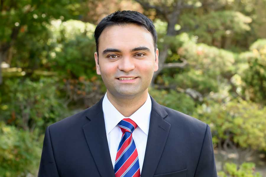 Dr. Jaspreet Parihar in a suit and tie, standing outdoors.